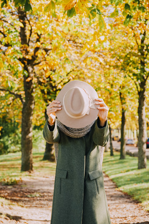 obscuring: Woman hiding her face behind hat LANG_EVOIMAGES