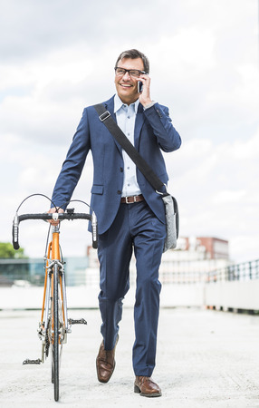 Businessman pushing bike while talking on the phone LANG_EVOIMAGES