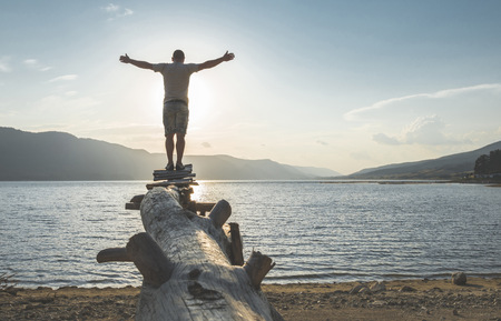Bulgaria, Rhodope Mountains, man with outstretched arms standing at shore of Dospat Reservoir