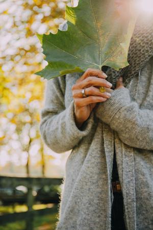 Woman holding autumn leaf LANG_EVOIMAGES