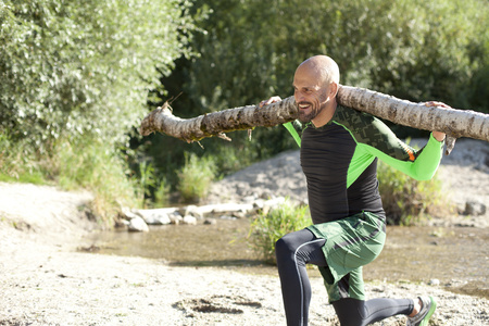 motivations: Man doing crossfit exercise with tree trunk on his shoulders