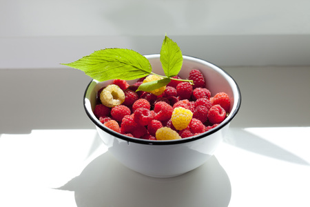 Bowl of red and yellow raspberries on window sill LANG_EVOIMAGES