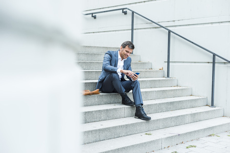 motivations: Businessman sitting on stairs using smart phone