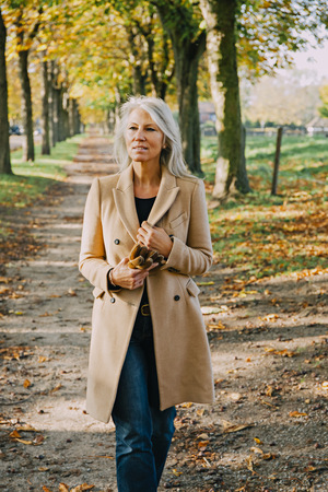 likeable: Portrait of woman walking in autumnal park