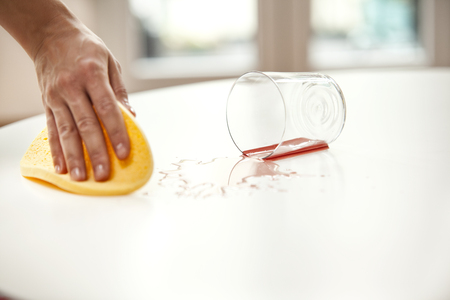 Woman wiping liquid from table from glass fallen down