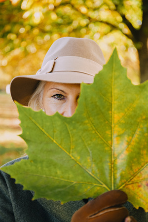 one mature woman only: Woman wearing hat hiding behind an autumn leaf