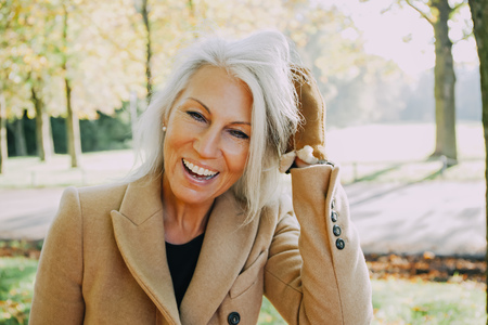 Portrait of laughing woman with hands in her hair in autumnal park