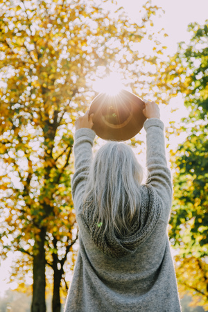 Back view of woman holding hat against the sun in an autumnal park LANG_EVOIMAGES
