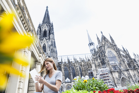 cabeza abajo: Germany, Cologne, young woman with digital tablet in front of Cologne Cathedral