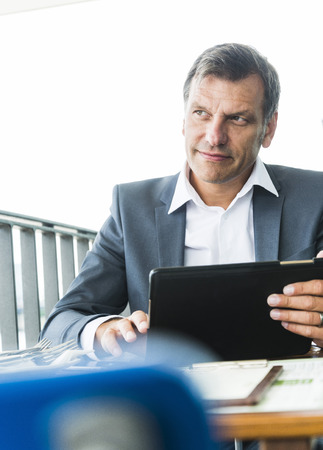 Businessman sitting outdoors, using digital tablet