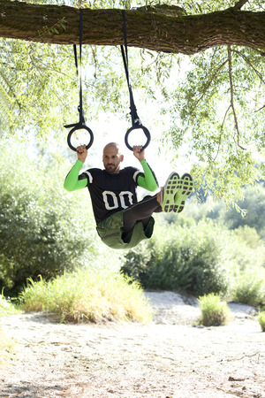 motivations: Man doing crossfit exercise on rings hanging on tree trunk