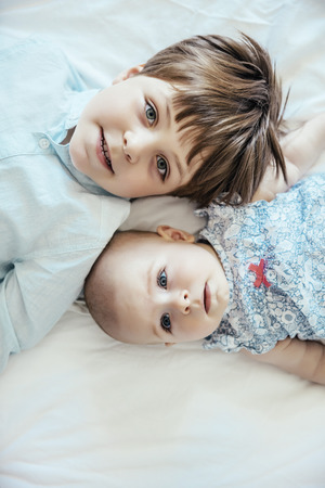 Baby girl and brother lying on bed LANG_EVOIMAGES