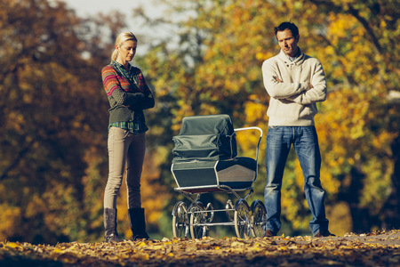 trouble free: Reserved couple standing with crossed arms looking at baby carriage at autumnal park