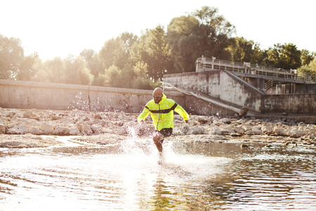 Man in sports wear running in water LANG_EVOIMAGES