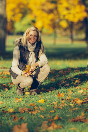 cowering: Woman crouching on a meadow in a park holding autumn leaves