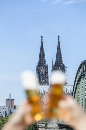 Germany, Cologne, couple toasting with Koelsch glasses in front of Cologne Cathedral