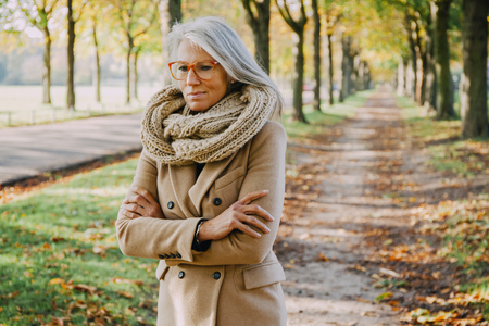 likeable: Portrait of woman wearing scarf and glasses walking in autumnal park