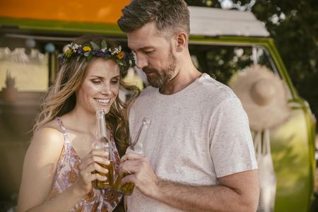Couple having a beer in front of van