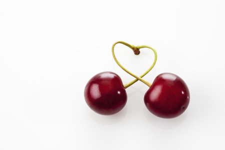 Stems of two sour cherries shaping a heart on white ground LANG_EVOIMAGES