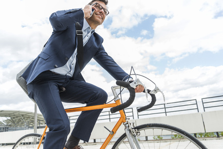 Businessman riding bicycle, talking on the phone LANG_EVOIMAGES