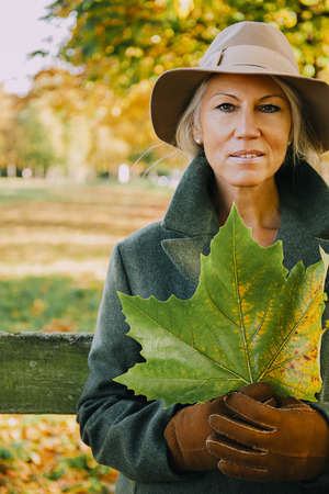 Portrait of woman wearing hat holding autumn leaf in a park LANG_EVOIMAGES