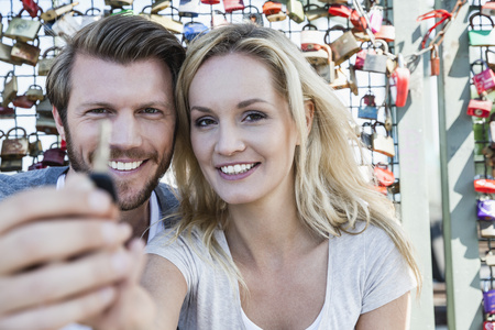 Germany, Cologne, portrait of smiling young couple holding key of love lock