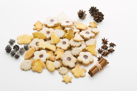 Different Christmas cookies, spices and pine cones on white ground