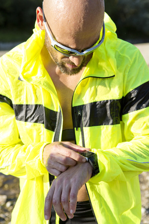 Man in sports wear adjusting his smartwatch LANG_EVOIMAGES