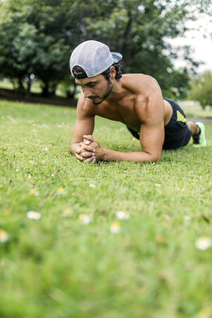 Athletic young man doing workout on a meadow in the park LANG_EVOIMAGES