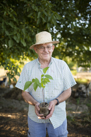 likeable: Portrait of smiling farmer with straw hat holding a plant in his hands