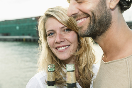 Happy couple drinking beer at the waterside LANG_EVOIMAGES