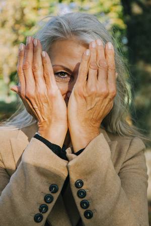 obscuring: Portrait of woman peeking through her hands LANG_EVOIMAGES
