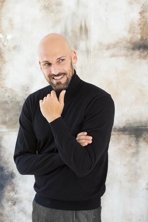 motivations: Portrait of smiling man wearing black turtleneck