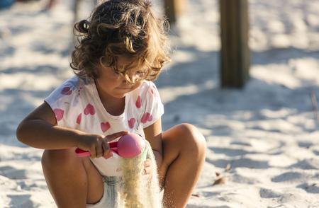 Little girl playing in sandbox on playground