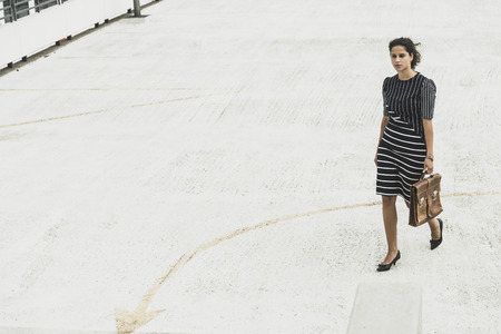 Young businesswoman walking on parking deck