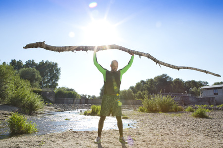 Man doing crossfit exercise with tree trunk on his shoulders