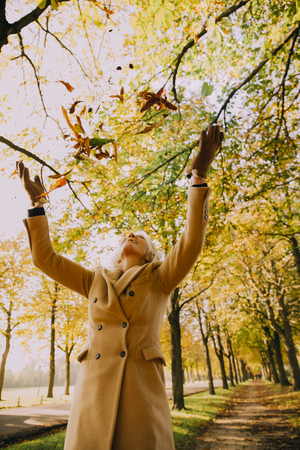 Woman throwing autum leaves in the air