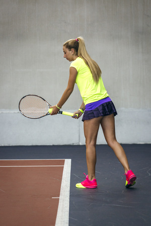 covered fields: Young woman playing tennis in an indoor tennis center