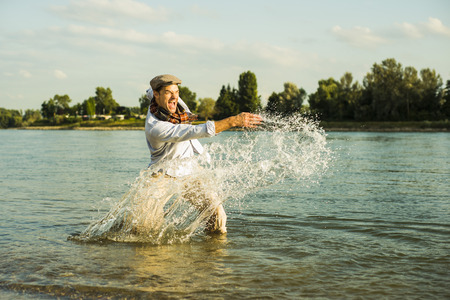ardor: Man standing in the river splashing with water LANG_EVOIMAGES