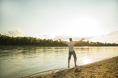 Back view of man standing at riverside with outstretched arms LANG_EVOIMAGES