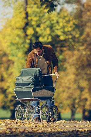 Father looking at his baby in pram in park on a sunny autumn day