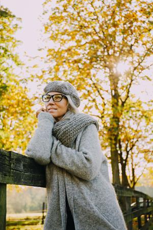 likeable: Portrait of woman wearing grey knitwear in an autumnal park