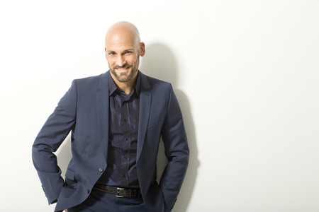 motivations: Portrait of bald man with beard wearing blue suit in front of white background