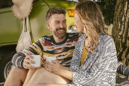 Couple having a hot beverage in front of van