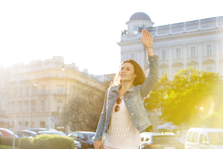 Poland, Warsaw, portrait of young woman hailing a taxi LANG_EVOIMAGES