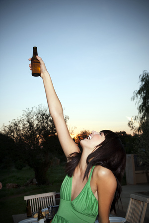 ardor: Happy young woman lifting a beer at sunset