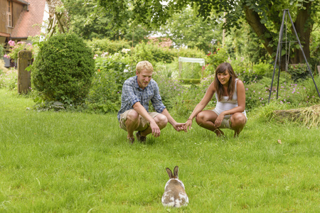 leporidae: Young couple expecting baby, crouching in garden, watching bunny