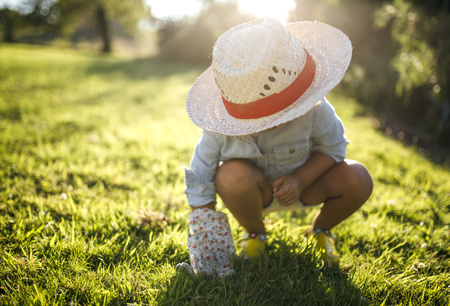 cowering: Little girl wearing straw hat crouching on a meadow