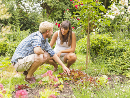 cowering: Young couple expecting baby, crouching in garden
