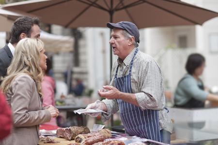 selling service: Man selling sausage at city market LANG_EVOIMAGES